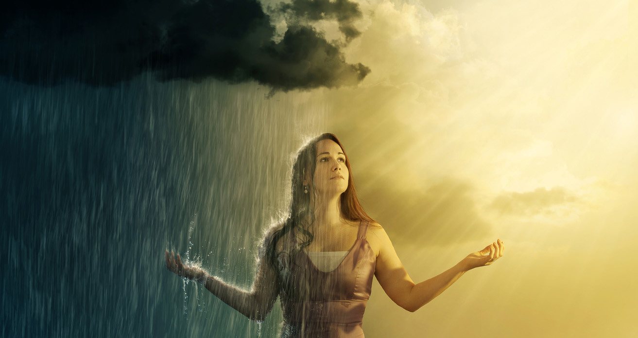 A woman stands under both a thunderstorm and sunny skies.